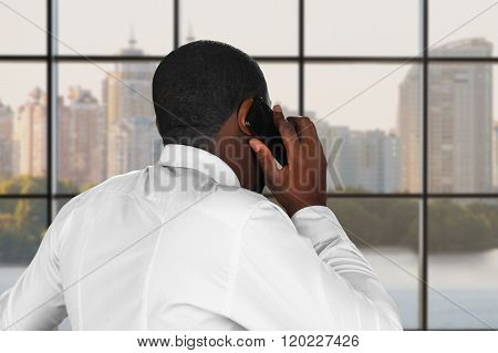 Composed phone conversation. Phonetalk next to a window. Executive is negotiating. Daytime negotiation in the city. poster