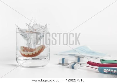 Dentures Concept With Glass, Mask And Toothbrush
