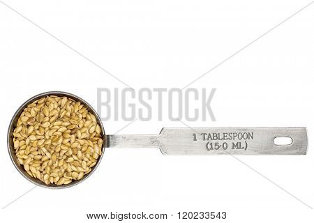 golden flax seeds in a metal measuring tablespoon isolated on white