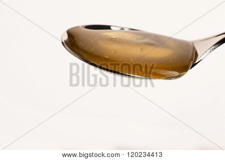 Spoon Filled With Sweet Golden Honey Isolated Over White Background.