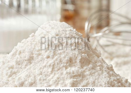 Heap of flour with whisk and baking ingredients in background.  Closeup with shallow dof.  Baking concept.