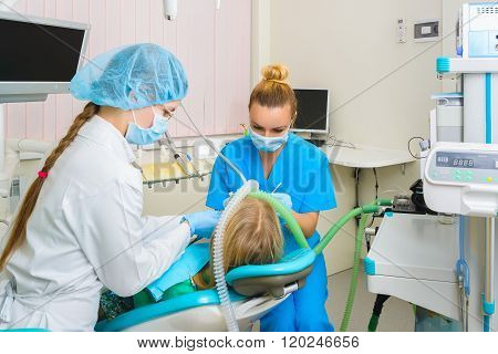 dentist performs a procedure of care for teeth child with deep anesthesia