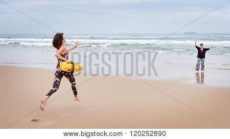 Mother pretending to need rescuing by her daughter beach side