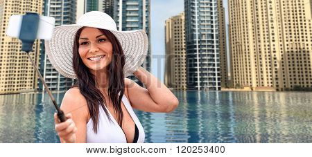 travel, tourism, summer, technology and people concept - smiling young woman in sun hat taking picture with smartphone on selfie stick over infinity edge swimming pool in dubai city background