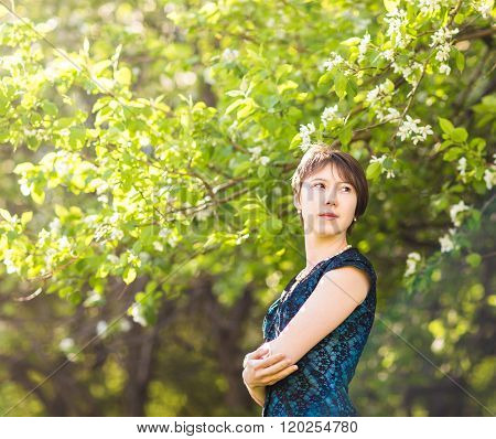 beauty, people, summer and spring  concept - beautiful young woman  over green blooming garden backg