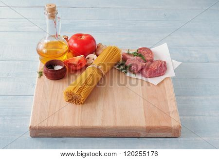 Spaghetti On Wooden Table With Tomatoes, Mushrooms, Meat And Oil