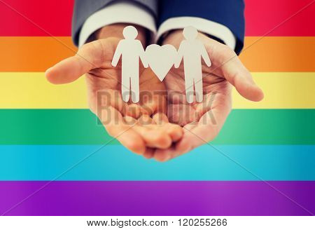 people, homosexuality, same-sex marriage and love concept - close up of happy male gay couple holding paper cutout love symbol over rainbow flag background