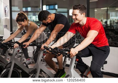 Three People Doing Spinning In A Gym