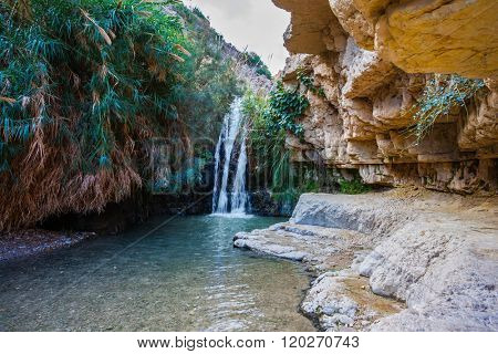 Pass under a rock in in the Ein Gedi Nature Reserve. The picturesque waterfall and a small deep lake with emerald water