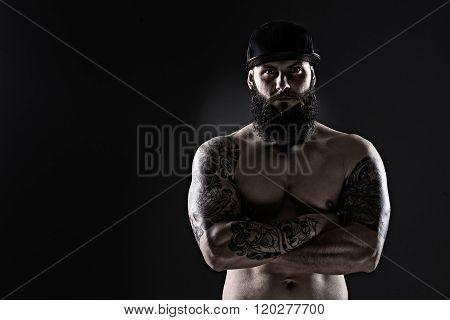 Studio Shot Of Muscular  Man With Tattoo On Dark Background