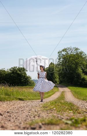 Woman In A Vintage Fifties Outfit Walking On A Path In The Nature