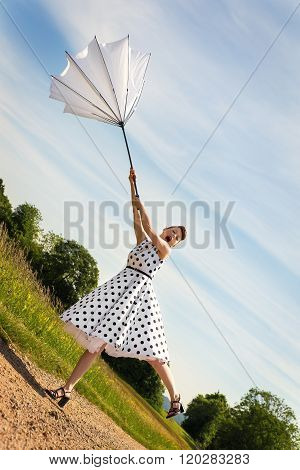 Pin Up Girl With A Umbrella Is Blowing Off The Path