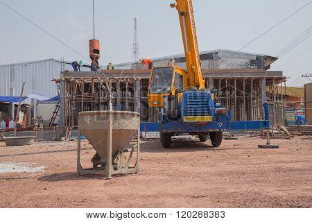 Crane Lifting Concrete Mixer Container At Construction Site
