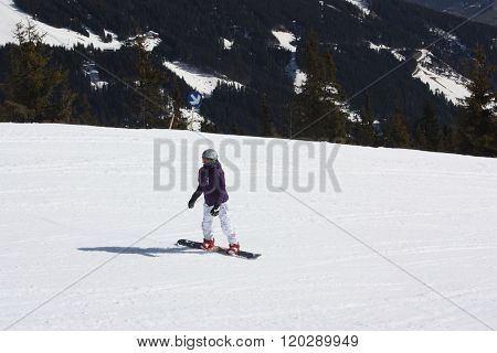Young lady snowboarder. Skiing resort in North Tirol.