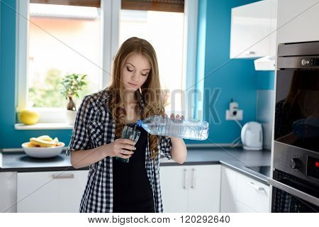 Woman In Kitchen Woman Pouring A Glass Of Water