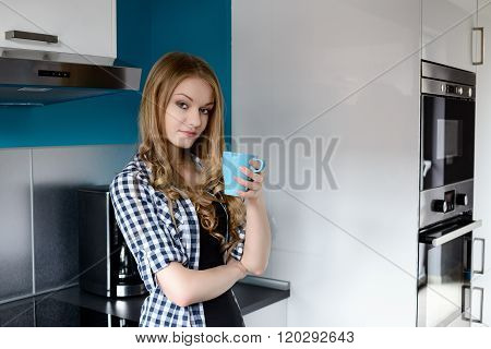 Beautiful Blonde Woman Drinking Coffee In The Kitchen