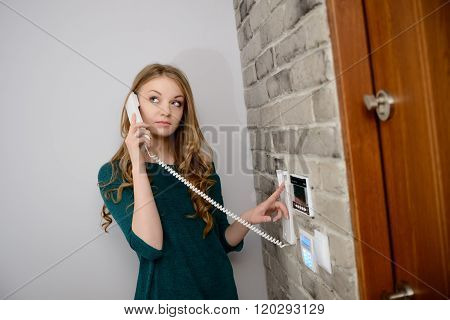 A Beautiful Young Blond Woman Talking On The Intercom