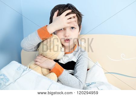 Sick Little Boy Hugs His Teddy Bear In Bed