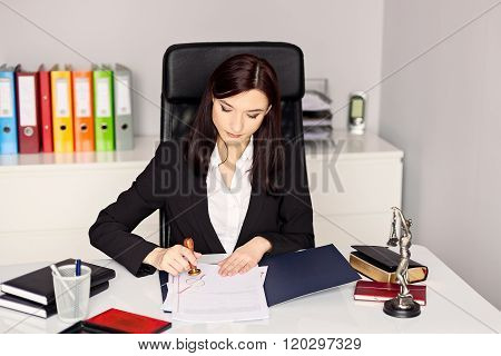 Woman Notary Public Stamping The Document In Her Office.