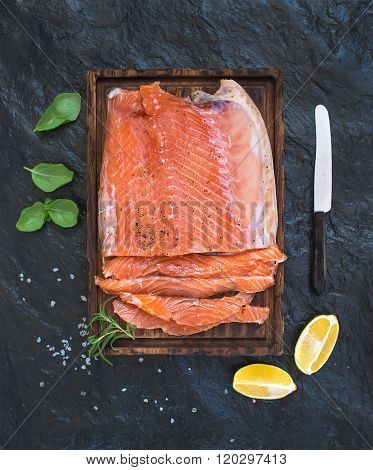 Smoked salmon filet with lemon, fresh herbs and bred on wooden serving board over dark stone backdro