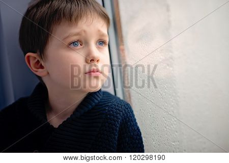 Child Waiting By Window For Stop Raining.