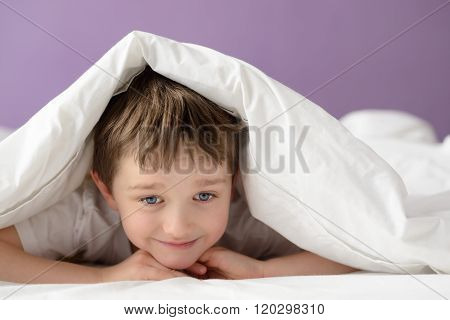 Happy Boy Playing In Bed Under A White Blanket Or Coverlet