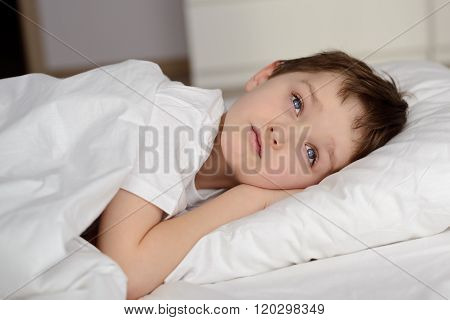7 Years Old Boy Resting In White Bed With Eyes Open