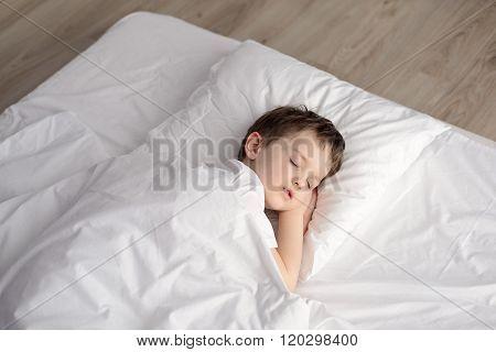 Tired Little Boy Sleeping In Bed, Happy Bedtime In White Bedroom