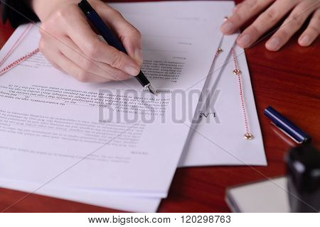 Closeup Of A Hand Signing A Last Will By A Pen.