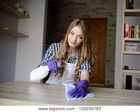 Young Woman Cleans A Wooden Table