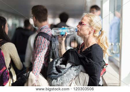 Woman drinking water while queuing to board plane.