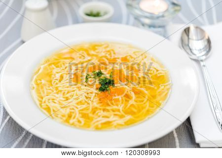 Plate Of Chicken Soup With Carrots And Noodles On White Plate
