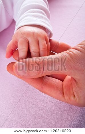 Mother s hand holding little hand of her baby