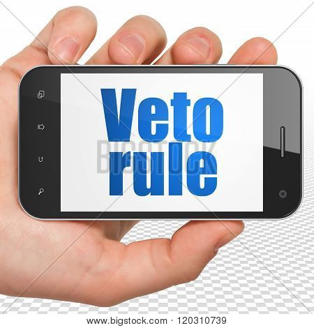 Political concept: Hand Holding Smartphone with blue text Veto Rule on display poster