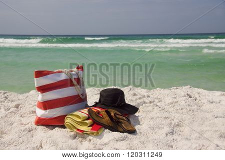 A beach bag floppy hat towel and Sandals at the beach.