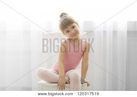 Little cute girl in pink leotard sitting on chair at dance studio