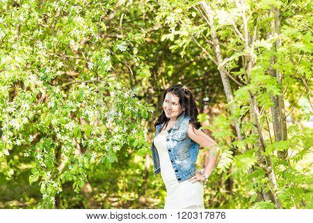 Spring woman in summer dress walking in green park enjoying the sun. Playful and beautiful mixed rac