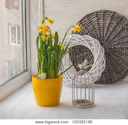 Vintage decoration window with a decorative cage and daffodils in yellow pot