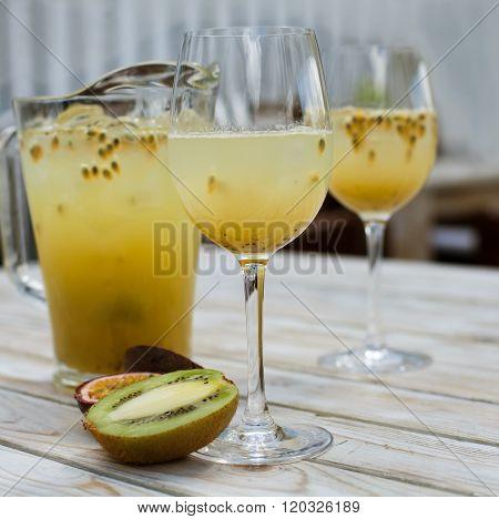 Lemonade with kiwi and passion fruit. Pitcher, slass  half tropical fruits on wood background