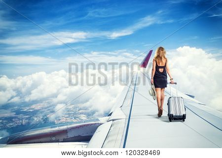 traveler woman walking on an airplane wing  carrying a suitcase Travel concept