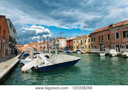 VENICE, ITALY - 17 OCTOBER 2015: Boats moored in a canal, Murano, Venice, Italy on the lagoon island of Murano known for its historic glass manufacturing
