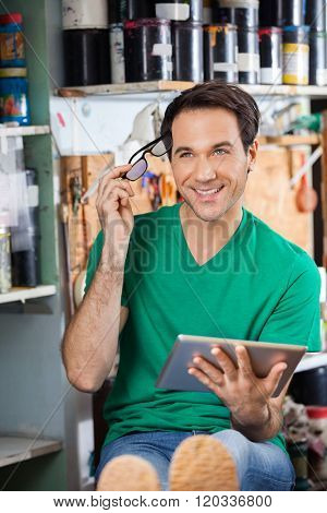 Thoughtful Worker Holding Eyeglasses And Tablet Computer In Fact