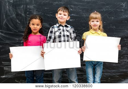 three cute children with empty paper sheets in hands and chalky blackboard on background