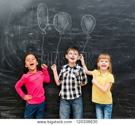 three joyful laughing children keep imaginary balloons drawn on the chalky blackboard