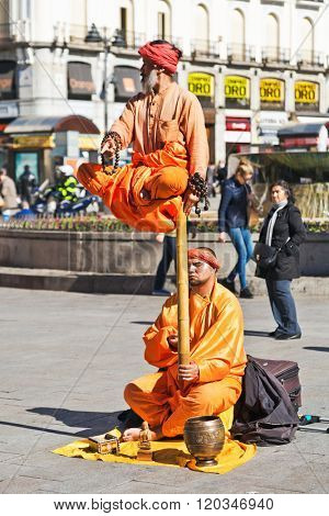 MADRID, SPAIN - OCTOBER 27, 2015 : Street performer in clothing monks demonstrates trick of levitation and strong power at Plaza de la Puerta del Sol in Madrid