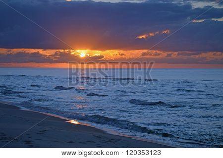 Dramatic sunrise on Pensacola Beach, Florida, over incoming tide.