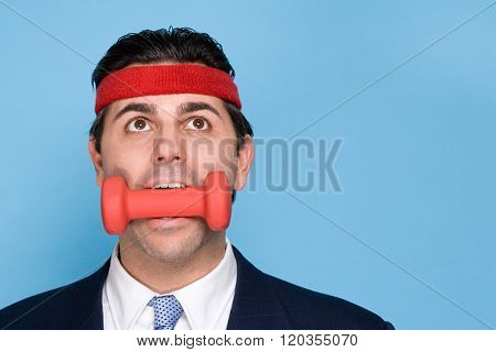 Businessman with a dumbbell in mouth