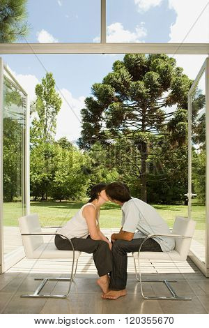Couple sitting in chairs and kissing