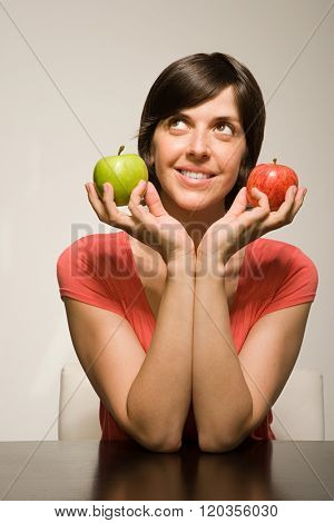 Woman holding green and red apples