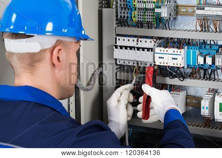 Close-up Photo Of Male Electrician Repairing Fusebox poster